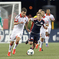 D.C. United midfielder Chris Pontius (13) brings the ball forward as New England Revolution midfielder Scott Caldwell (6) defends. In a Major League Soccer (MLS) match, the New England Revolution (blue) tied D.C. United (white), 0-0, at Gillette Stadium on June 8, 2013.