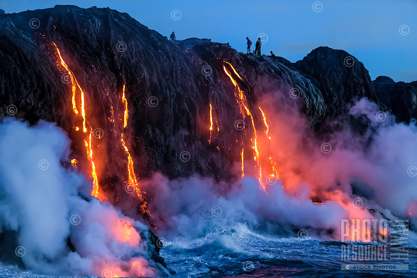 At dawn on the 30th anniversary of Kilauea's eruption, lava enthusiasts observe lava flowing into the ocean along the border of Hawai'i Volcanoes National Park on the Big Island.