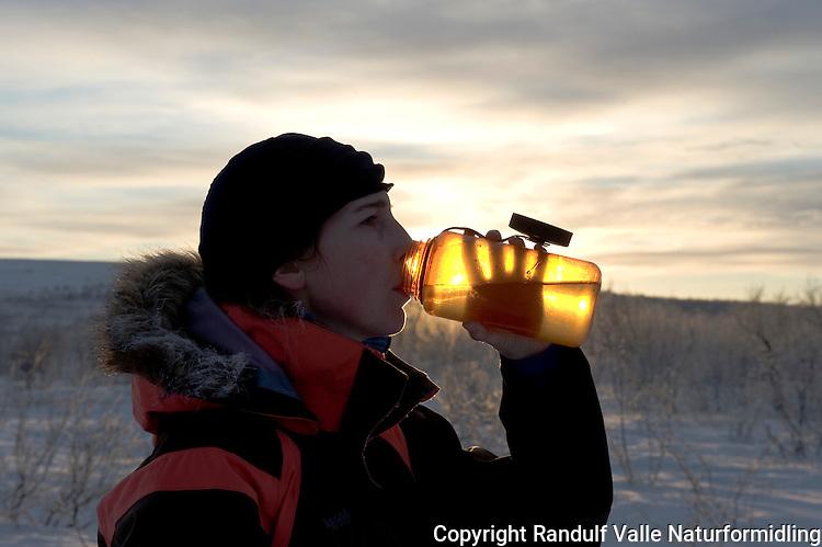 Dame med rim i pelskragen drikker vann. ---- Woman drinking water.