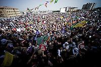 """Un immense rassemblement est organisé par les femmes dans le quartier récent de Newroz à Nusaybin. Elles viennent de toute la région marquer l'espace de la ville de leur combat. L'ambiance est délirante. La foule de femme hurle et danse toute la journée. Les femmes politiques se relient sur l'estrade pour chauffer la foule. Des chansons révolutionnaires résonnent sur les toits de la ville. Le son porte évidemment jusqu'en Syrie, la frontière est à 500 mètres. Les principaux slogans sont """"nous réussirons malgré les frontières"""" et """"Jin, Jiyan, Azadî"""" qui peut se traduire par """"la femme, la vie, la liberté""""."""