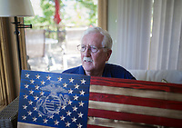 NWA Democrat-Gazette/CHARLIE KAIJO Don Lowe sits for a portrait holding an American flag he and his grandson Jeremiah Lowe, 11, (not pictured) created out of wood pieces, Monday, August 12, 2019 at his home in Bella Vista.<br /> <br /> Don Lowe and his grandson, Jeremiah Lowe, 11, turned their woodcrafting hobby into a business nine months ago after Don sold one of his wooden flags on Facebook within the first hour of posting it. It's a casual hobby he and his grandson share but they've sold 30 now in over four states, many to retired and active service members and emergency responders. He is working on a wooden flag he and his grandson will donate to the Bella Vista Fire Department.
