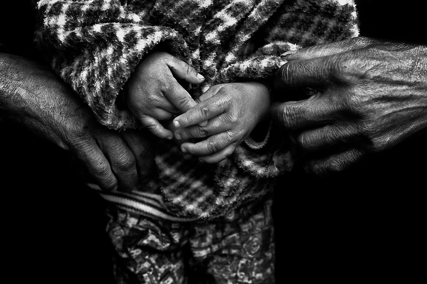 A father holds his son in a refugee camp in eastern Kachin State.
