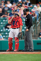 Pawtucket Red Sox catcher Dan Butler (12) talks with home plate umpire Chris Graham during a game against the Rochester Red Wings on May 19, 2018 at Frontier Field in Rochester, New York.  Rochester defeated Pawtucket 2-1.  (Mike Janes/Four Seam Images)