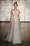 Model walks runway in a deep v front u back tulle ballerina dress with feather embroidery, from Inbal Dror Fall 2018 bridal collection on October 5, 2017; during New York Bridal Fashion Week.