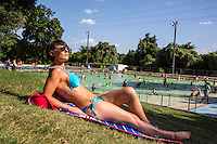 Beautiful young woman with dark tan in bikini sunbathing at Deep Eddy Pool in Austin, Texas.