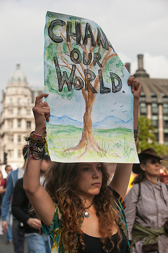 A protester holds a placard which says 'Change Our World' with a picture of a tree as she marches into Westminster Square during the Climate Change demonstration, London, 21st September 2014. © Sue Cunningham