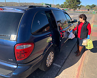 Lydia Velasco, an ESL aide at Greenland Elementary School, distributes bags Saturday, March 21, 2020, during a giveaway of food and household items at the school. The school, along with Lincoln, Gravette and Pea Ridge, partners with Essentials Outreach to provide necessary items to families in its district on third Saturday of the month. After serving 27 families in its first month last month, Greenland gave items to 271 individuals on Saturday. Visit nwaonline.com/200322Daily/ for today's photo gallery.<br /> (NWA Democrat-Gazette/Andy Shupe)