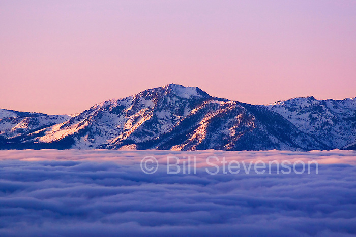 A photo of sunrise and a sea of clouds over Lake Tahoe and Mount Tallac in winter in Nevada