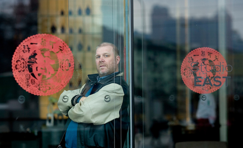Glaston executive Pekka Nieminen poses behind glass and paper cuts with the Chinese character 'Fu' for 'Happiness' for a photograph in Shanghai, China, on February 1, 2009.  The character is placed on purpose upside down to make a play on words between 'upside down' and 'arrives' which are homophenic in Chinese. Therefore it can be read as 'happiness arrives'. Photo by Lucas Schifres/Pictobank