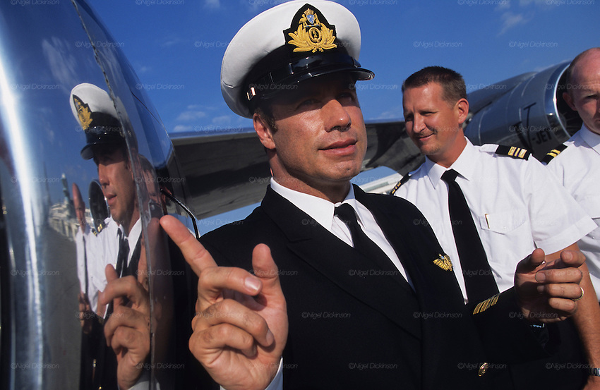 """John Travolta is reflected in the fuselage of the plane which he is captain and pilot, his own jumbo jet...John Travolta is pilot of his very own jumbo jet, a 1964 Boeing 707-100 series. In 2003, John Travolta flew his jumbo jet around the world, in partnership with Quantas, to rekindle confidence in commercial aviation, and to remind us that elegance and style are a part of flying. The crew are dressed in tailor made authentic uniforms from the Quantas museum. The men's uniforms are styled on British Naval uniforms and the ladies' designed by Chanel. His jumbo jet sports a personalised number plate N707JT which speaks for itself. The aircraft is named """"Jett Clipper Ella"""" dedicated to his son and daughter. This jumbo together with his other aircraft are housed in purpose built hangars at his home in Florida, USA."""