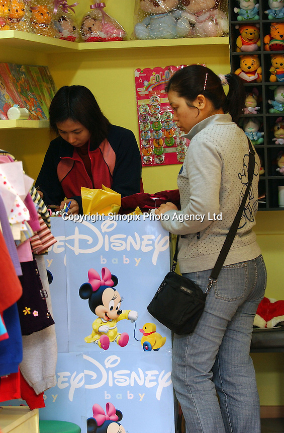 A lady buys a Disney brand coat in Guangzhou, China..11-DEC-04
