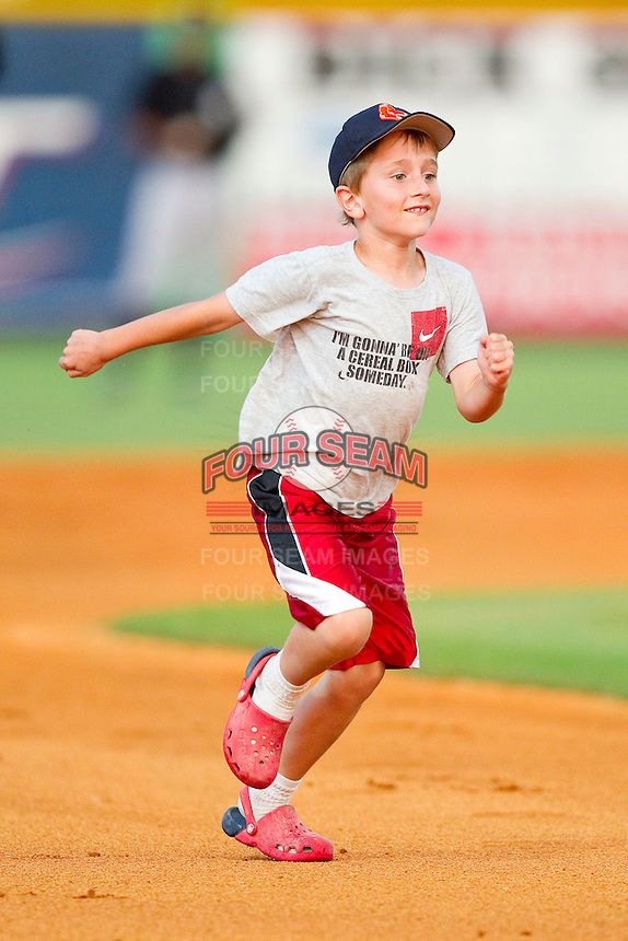 A young fan hustles towards third base during the mascot race between innings of the Appalachian League game between the Bristol White Sox and the Burlington Royals at Burlington Athletic Park on July 6, 2012 in Burlington, North Carolina.  The Royals defeated the White Sox 5-2.  (Brian Westerholt/Four Seam Images)