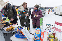Bob Bundtzen, right, eats a hamburger in the staging area prior to the restart of the Iditarod sled dog race in Willow, Alaska Sunday, March 3, 2013.