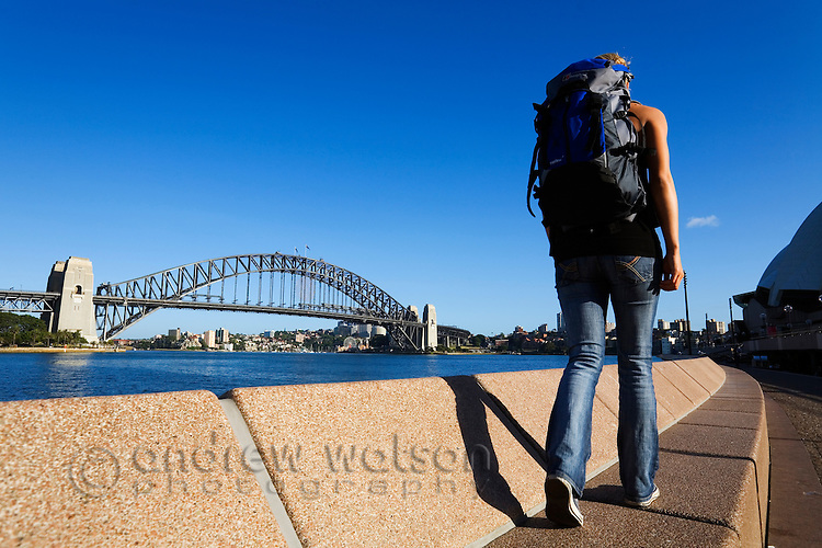 A backpacker walks along the Sydney Harbour waterfront.  Sydney, New South Wales, AUSTRALIA.