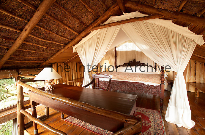 The bedroom of a boutique style luxurious wooden treehouse, made entirely of wood and grass. The interior has a rustic feel, with the talents of regional artists adding many of the finishing touches.