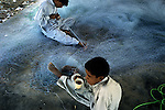 Young boys mend fishing nets in the seaside town of Jiwani.  Lying close to the border with Iran, Jiwani is departure point for many Balochi families visiting relatives on the other side of the international border between Pakistan and Iran