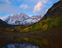 White River National Forest, CO: Morning clouds, snow dusted Maroon Peaks with fall colored aspens in the Maroon Bells-Snowmass Wilderness