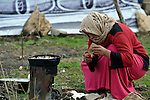 "A woman refugee from Syria lights a stove as she prepares food for her family. They live in a rented ""tent""--made from a billboard canvas of a dollar bill--in the village of Jeb Jennine, in Lebanon's Bekaa Valley. They and other refugee families in the area are being assisted by International Orthodox Christian Charities and other members of the ACT Alliance.."