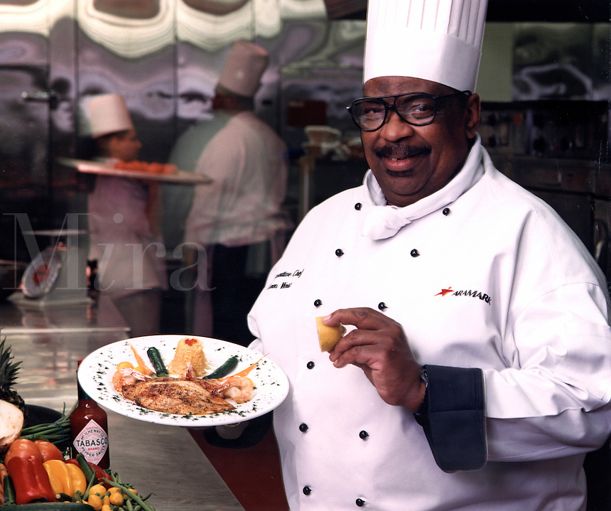 A smiling African American chef in uniform puts the finishing touches on a plate of food. Louisiana.