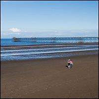 Couple walking on beach towards the pier