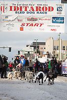 Rohn Buser and team leave the ceremonial start line with an Iditarider at 4th Avenue and D street in downtown Anchorage, Alaska during the 2015 Iditarod race. Photo by Jim Kohl/IditarodPhotos.com