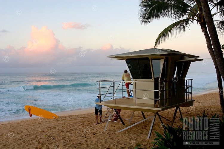 Lifeguards watch the beach at Ehukai Beach park (Banzia pipeline) as the sun sets on the north shore of Oahu.