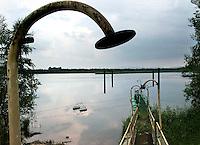 TSCHECHIEN, 07.2006 .Mydlovary.Eines der MAPE-Abseztbecken fuer radioaktive Abwaesser. Die fruehere Uranverarbeitungsanlage bei Mydlovary, MAPE, liegt in Suedboehmen. Zwischen 1962 und 1991 produzierte sie 28525 Tonnen Yellow Cake fuer sowjetische Nuklearwaffen und einheimische AKW. Die Reste des Trennprozesses von Erz und Uran wurden in Absetzbecken rund um die Anlage gepumpt. Dort lagern heute 36 Millonen Tonnen radioaktiver Schlaemme. Boden, Wasser und Luft weisen erhoehte Schwermetall- und Strahlenwerte auf..© Vaclav Vasku/EST&OST.One of the MAPE tailing ponds for radioactive waste water. The former chemical processing plant of uranium ore near Mydlovary, MAPE, is situated in Southern Bohemia. Between 1962 and 1991, 28525 tons of yellow cake were produced for Soviet nuclear bombs and domestic power plants. The uranium was separated from the ore by acid and alcalic leaching. The residue was stored in tailing ponds close to the plant. These contain a total of 36 million tons of radioactive sludge. Soil, water and air show raised levels of radioactivity and heavy metals.