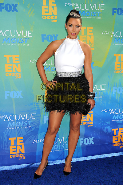 Kim Kardashian.2011 Teen Choice Awards - Arrivals held at Gibson Amphitheatre, , Universal City, California, USA..August 7th, 2011.full length white sleeveless hair up bun top black skirt hand on hip feathers .CAP/ADM/BP .©Byron Purvis/AdMedia/Capital Pictures.