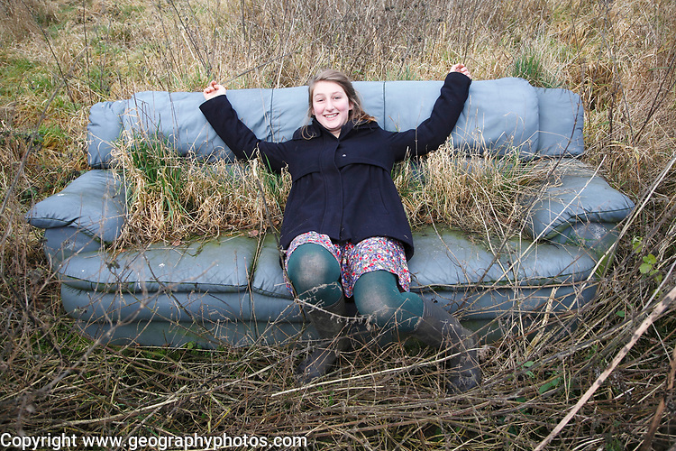 Young woman sitting outdoors in old settee couch overgrown with grass and weeds, UK