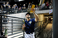 Tim Tebow (15) of the Columbia Fireflies signs a book for a fan before heading down the tunnel to the clubhouse after a game against the Lexington Legends on Thursday, June 8, 2017, at Spirit Communications Park in Columbia, South Carolina. Columbia won, 8-0. (Tom Priddy/Four Seam Images)