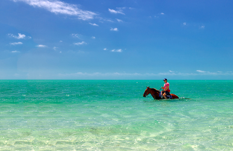 Horse rider in water. Providenciales. Turks and Caicos.