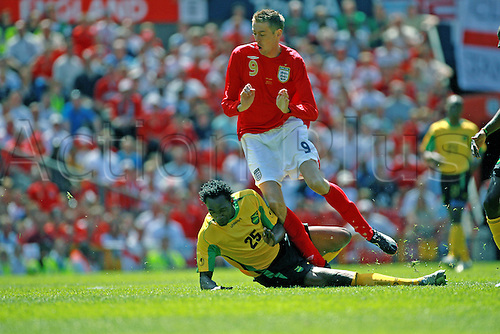 3 June 2006: England striker Peter Crouch is tackled by Jamaica defender Claude Davis during the International Friendly match between England and Jamaica played at Old Trafford, Manchester. England won the game 6-0. Photo: Steve Bardens/actionplus...060603 soccer football man male men foul slide tackle tackling