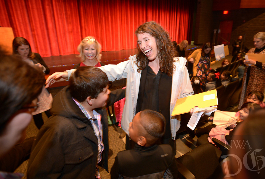 NWA Democrat-Gazette/ANDY SHUPE<br /> Allison Dingler (center), an English as a second language teacher at Woodland Junior High School, smiles Thursday, Nov. 8, 2018, as she greets former student Bryan Soto, 10, during The Fayetteville Public Schools English as a Second Language Program's ceremony to honor English learners who have met the Arkansas Department of Education&rsquo;s criteria to exit the ESL program at the Fayetteville High School Performing Arts Center. The program celebrated 144 participants during the district's first exit ceremony.