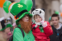 Reveller dressed as a leprechaun with a child participates in a Saint Patrick's day celebration march in Budapest, Hungary on March 17, 2013. ATTILA VOLGYI