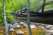 Hiker crossing footbridge along the Thoreau Falls Trail at North Fork Junction in Pemigewasset Wilderness of Lincoln, New Hampshire. This bridge crosses the East Branch of the Pemigewasset River, and it has a noticeable tilt.