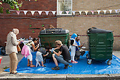 Local residents re-paint recycling bins at a Tell It Parents Action Group street event to launch a drop-in advice service on the Mozart Estate, North Westminster, which has experienced problems with postcode gang violence.