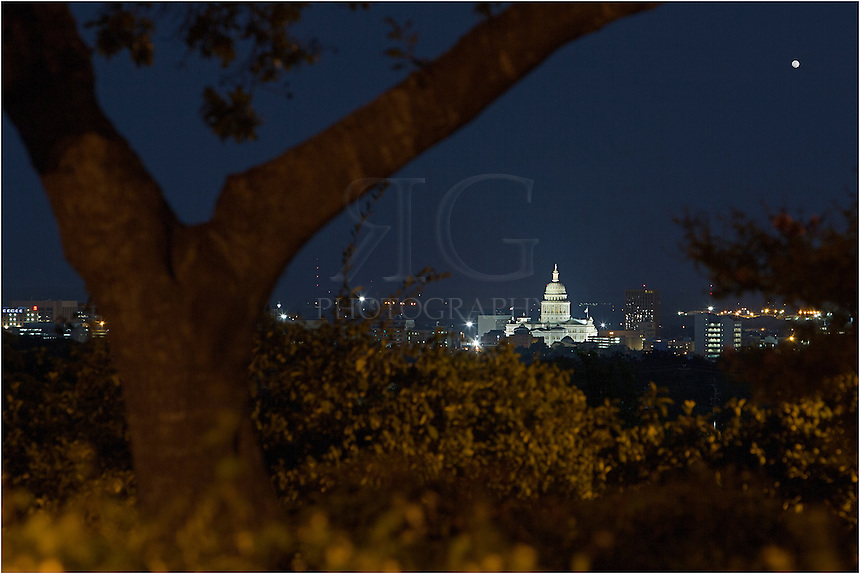 Looking through an old oak tree just off the 360 Loop around Austin, Texas, this photo shows the state capitol in the evening as a moon rises in the east.