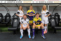 Pictured front L-R: Players Leon Britton with home kit and Ben Davies with away kit surrounded by local female models. <br /> Re: Official launch of the 2013-2014 Swansea City Football Club kit launch, with sponsors Goldenway GWFX at the Liberty Stadium, Swansea, south Wales. Friday 28th of June 2013