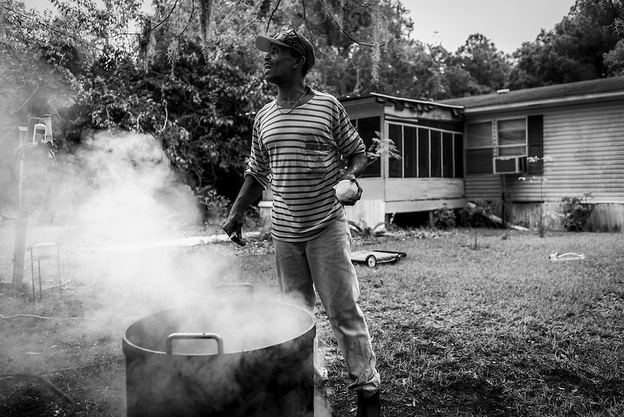 Daufuskie Island native Al Smith prepares to steam some clams and conch in front of his home. Like most of the Gullah, Smith lives off of the sea and the land as much as possible.
