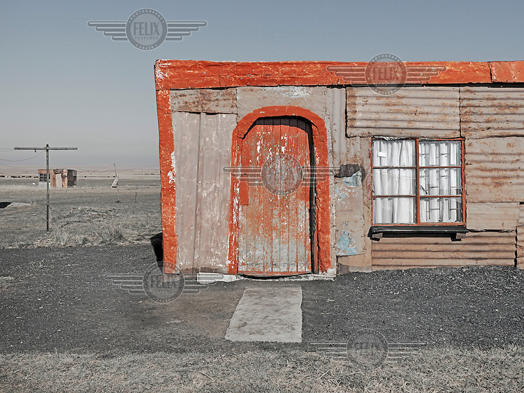 A corrugated iron shack whose doors and roof are decorated with fading red paint.  Graeme Williams' pictures of the environments occupied by some of South Africa's poorest people focus on the interiors and exteriors of people's homes, accentuating the minutiae of the occupants' day-to-day dwelling places. The bright colours captured in these photographs are suggestive of resilience, hope and a sense of humanity that survives in these poverty-stricken communities...
