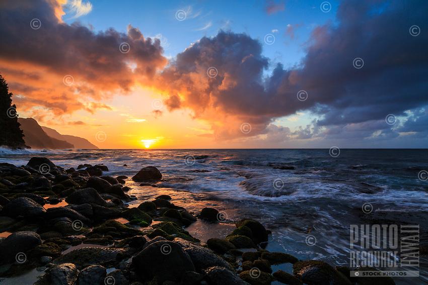 The sun sets on the Na Pali coastline, seen from Ke'e Beach, Ha'ena, Kaua'i.