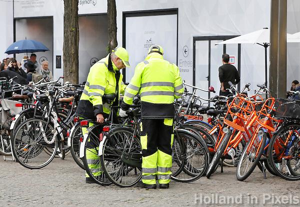 Nederland  Amsterdam  2016. Medewerkers van de gemeente verplaatsen fietsen op de Dam om meer loopruimte te creeren. Foto Berlinda van Dam / Hollandse Hoogte