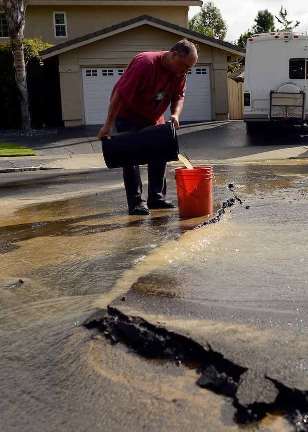 Edwin Wilkerson collects water to clean his kitchen from a broken water main, which cut off water service to his home, after a magnitude 6.0 earthquake struck in the early morning of August 24, 2014, in Napa, California.
