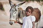 A girl poses with her family's donkey in Picmy, a village on the Haitian island of La Gonave where Service Chr&eacute;tien d&rsquo;Ha&iuml;ti is working with survivors of Hurricane Matthew, which struck the region in 2016. SCH, a member of the ACT Alliance, supports agriculture on the island by providing tools, seeds, and technical support and training for farmers. It also provided donkeys to many families. In Pierre's case, the donkey helps her bring water from a long distance to her family. <br /> <br /> Parental consent obtained.