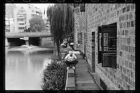 A Chinese chef plays with his mobile phone along a canal at the old city centre in Ningbo of Zhejiang province in eastern China, September 2016.