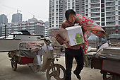 Chen Hua, 50, moves into her new urban home in a northeastern China.<br /> <br /> Her former village house was bulldozed by the government three years ago to make way for high-rise development. <br /> <br /> In the four years between her rural home being razed and the completion of her new city apartment, she and her family lived in temporary village housing such as this one. <br /> <br /> China is pushing ahead with a dramatic, history-making plan to move 100 million rural residents into towns and cities between 2014 and 2020 &mdash; but without a clear idea of how to pay for the gargantuan undertaking or whether the farmers involved want to move.<br /> <br /> Moving farmers to urban areas is touted as a way of changing China&rsquo;s economic structure, with growth based on domestic demand for products instead of exporting them. In theory, new urbanites mean vast new opportunities for construction firms, public transportation, utilities and appliance makers, and a break from the cycle of farmers consuming only what they produce.<br /> <br /> Urbanization has already proven to be one of the most wrenching changes in China&rsquo;s 35 years of economic reforms. Land disputes rising from urbanization account for tens of thousands of protests each year.