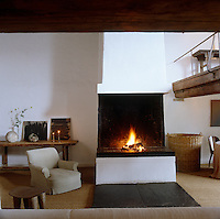 Two large slabs of slate are placed, rug-like, on the floor in front of this open fireplace with a small armchair to one side