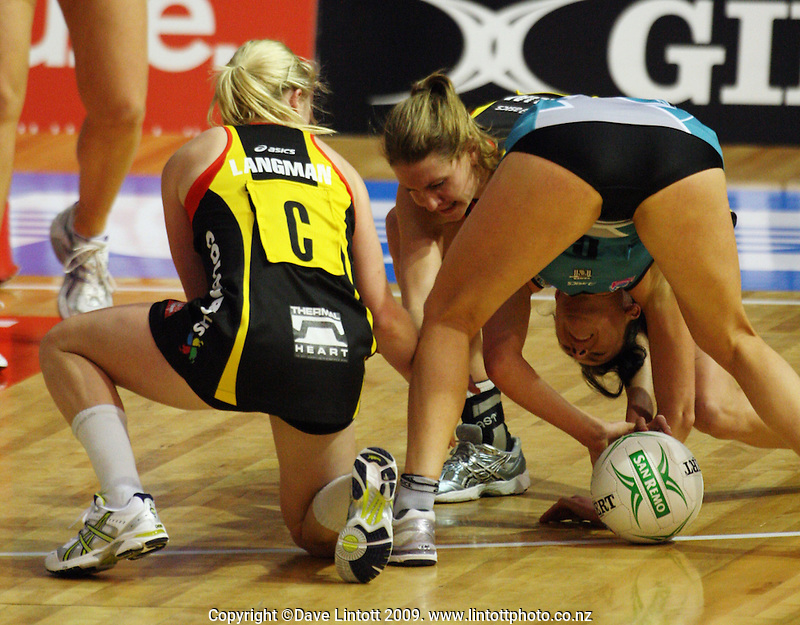 Laura Langman (left) and Casey Williams try to get the ball off Thunderbirds captain Natalie Von Bertouch during the ANZ Netball Championship match between the Waikato Bay of Plenty Magic and Adelaide Thunderbirds, Mystery Creek Events Centre, Hamilton, New Zealand on Sunday 19 July 2009. Photo: Dave Lintott / lintottphoto.co.nz