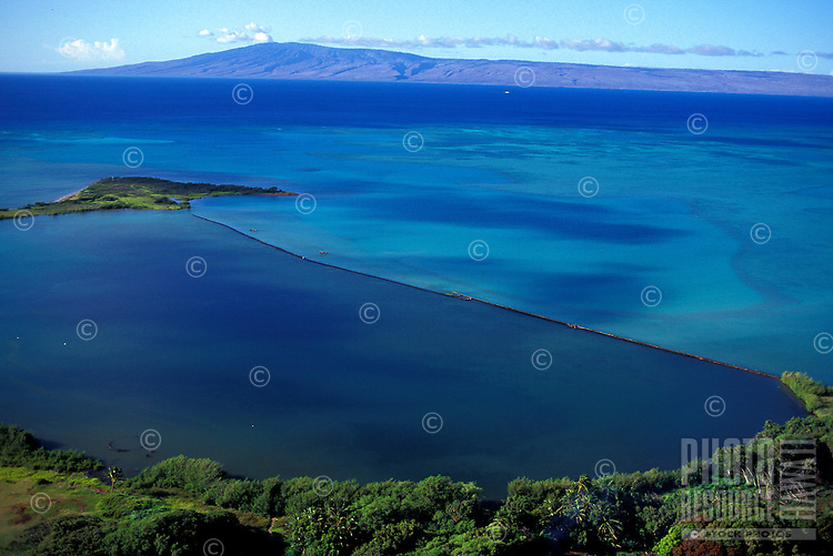 Aeriel view of the restored Keawanui Fishpond on the southeastern coast of Molokai, with the island of Lanai in the background