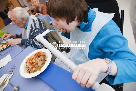 Young disabled client who has Cerebral Palsy using Neata Eater device to eat lunch at a resource for people with physical and sensory impairment.